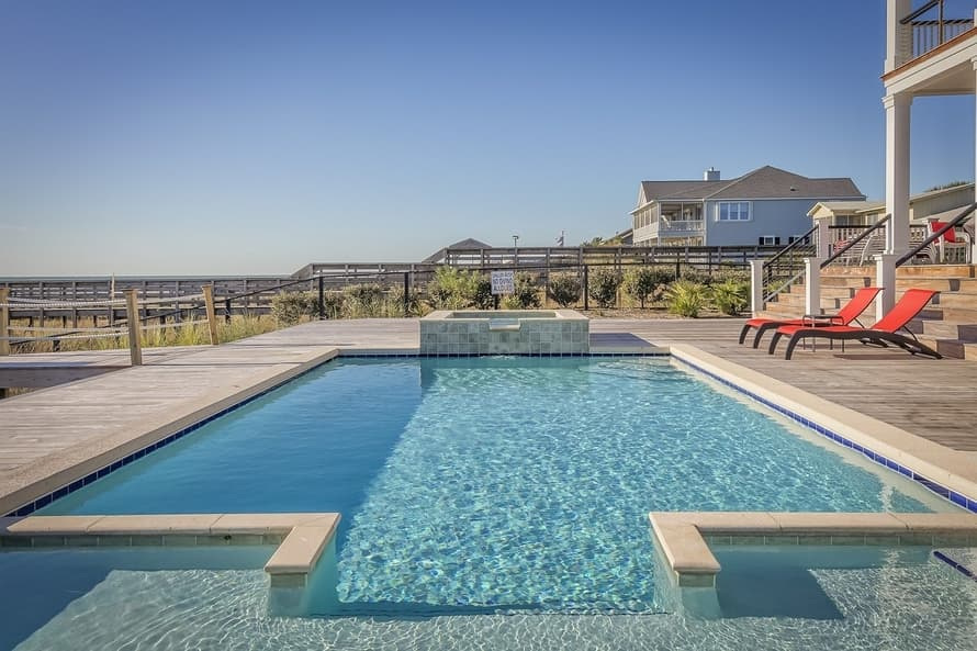 Beautiful blue pool with concrete pool deck overlooking the beach