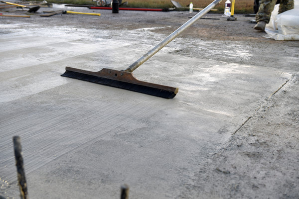 Smoothing a concrete parking lot and finishing with a concrete broom